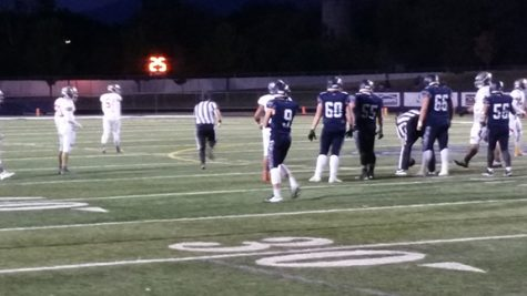 Dylan Robson, playing football against Skyridge. He is doing this to contribute to possibly winning. Does this by playing football. Taken on September 16, 2016 at the Corner Canyon football stadium.
