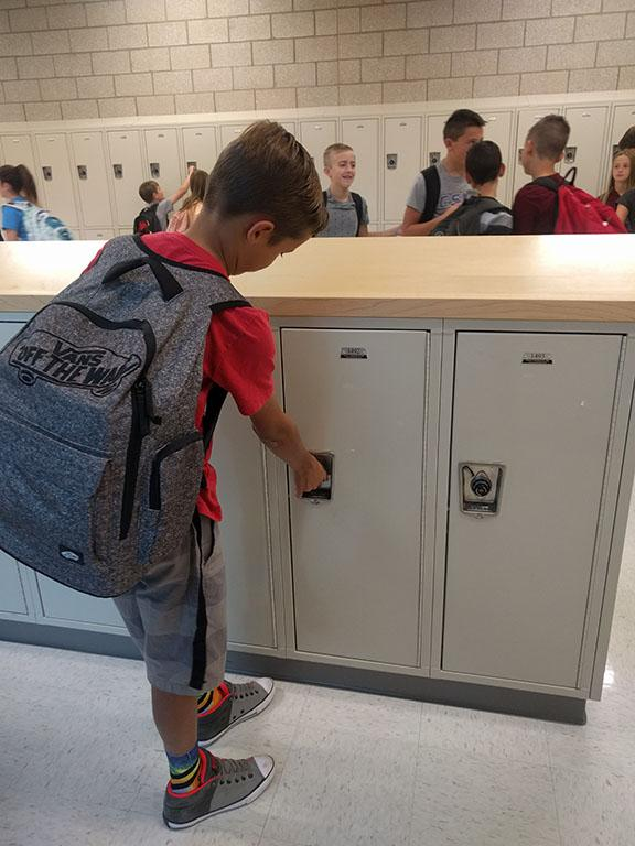 6th grader opens his locker to get his books before class.
