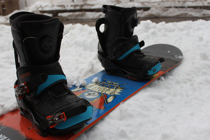 A snowboard sits in the snow with the boots locked in.