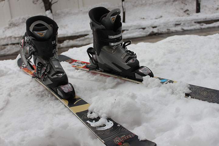 Skis and boots are stuck into deep snow.