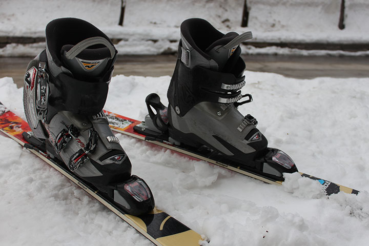 The bindings of these ski boots are shown locked onto the skis.