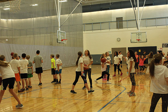 The sixth graders in PE are learning and practicing basketball at the school's gym.