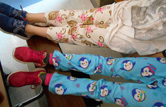 """7th graders, Katie Burnett and Rachel Oldham have sprawled their legs onto the nearby bench with their cute pajama pants at lunch on pajama day, after they finished eating so that they could give their legs a """"rest""""."""