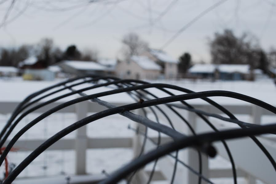 This is a picture of a roll of wire. Ponting toward the houses in the background.