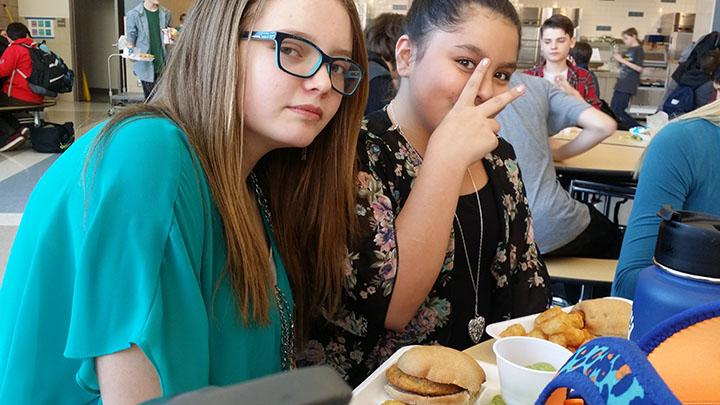 This is a picture of two students eating school lunch and liking it on February 16, 2017.