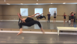 Claire Covey doing a flip in the air at her dance studio.