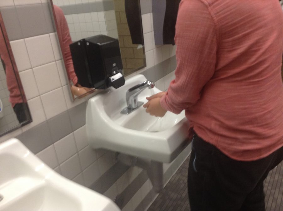 This is a photo of Isaac Varela washing his hands to conserve water.