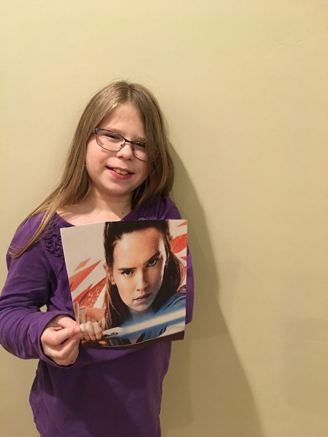 Emily Hardman holding a picture of Rey, the main character in Star Wars: The Last Jedi.