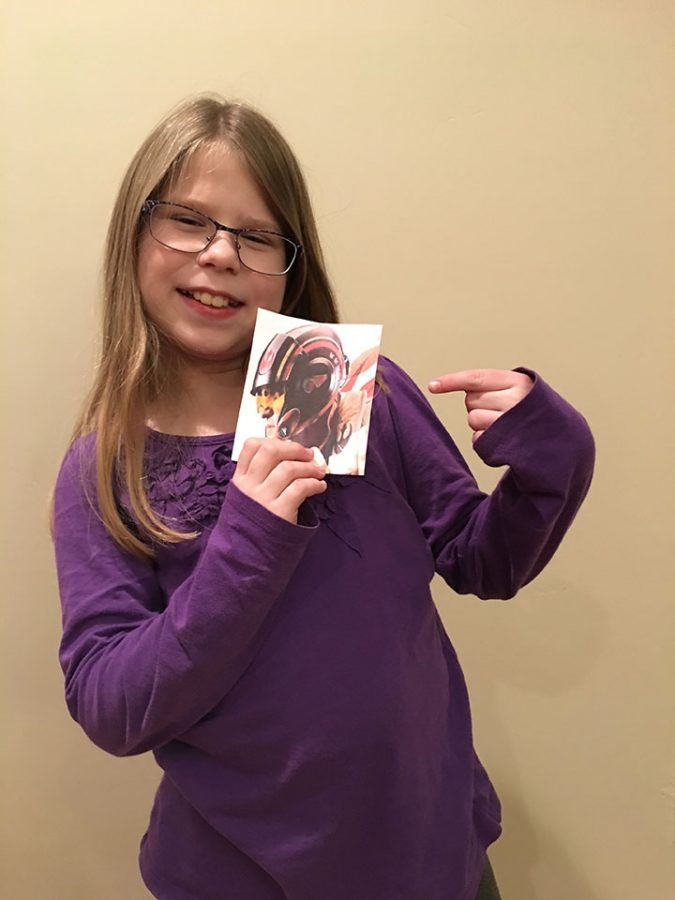 Emily Hardman holding a picture of a character from Star Wars: The Last Jedi.