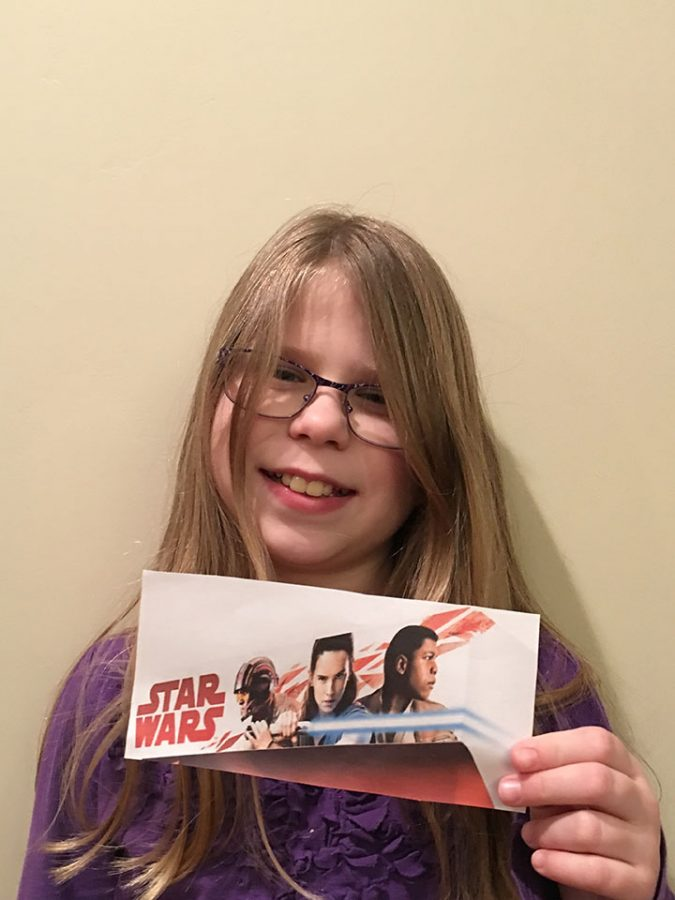 Emily Hardman holding a picture of three characters who are in Star Wars: The Last Jedi, on February 20, 2017.