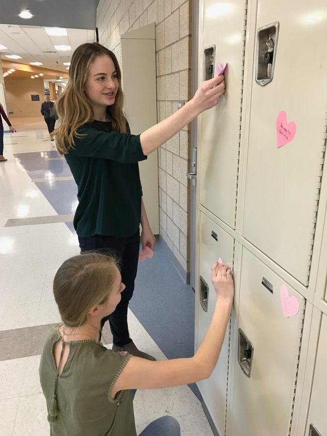 Mayson Jones 7th grader and Emerald Spencer 8th grader putting hearts on lockers during service club on February 13, 2017