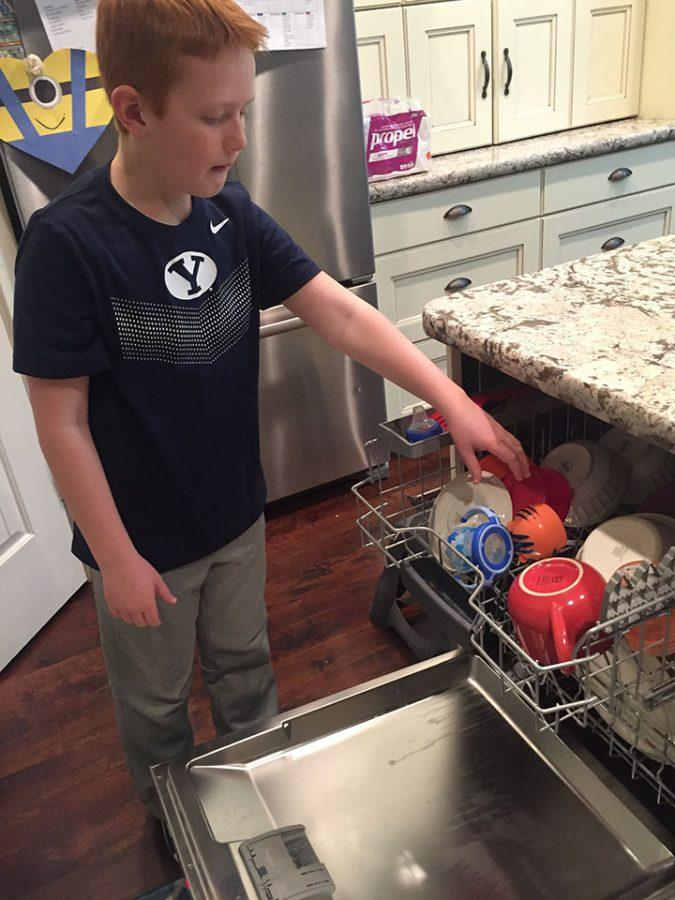 Teagan Johnson, student, empties the dishwasher as a chore to earn extra money.