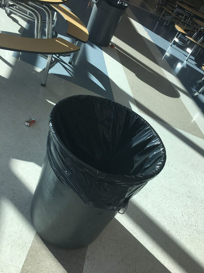This is an image of a trash can in the lunchroom. There is wasted drinks littered at the bottom of each trash can. This picture was taken on February 15, 2017 at Draper Park Middle School, which is located in Draper, Utah.