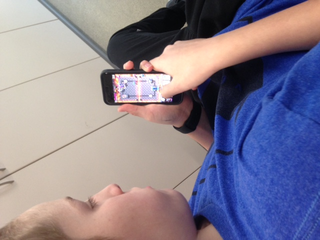 Brad Critchfield playing Clash Royale on his phone.