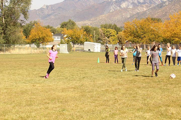 This is a photo was taken in November during the day. It is of the 6th graders in P.E. class, outside in the field, playing soccer.
