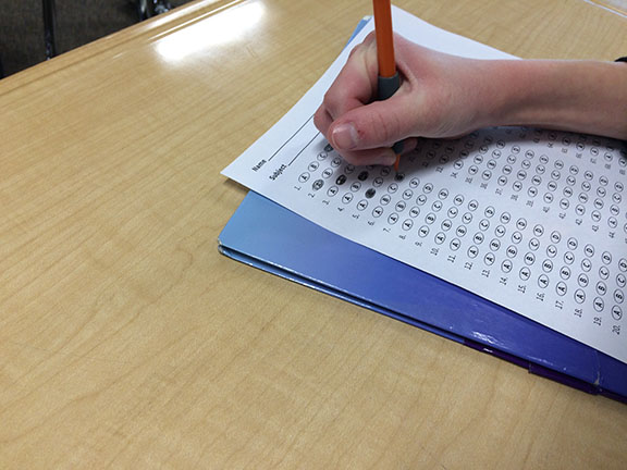A student is writing on their quiz paper in the math classroom on February 16.