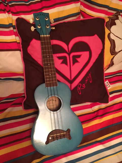 This is a ukulele, laying up against a cute pillow, 2/22/2017