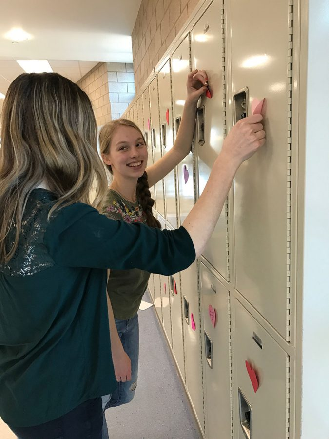 Emerald Spencer and Mayson Jones decorating lockers for valentines day during service club on February 13, 2017