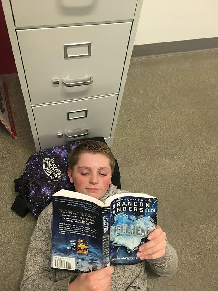 Colton Grimshaw laying down and reading a book 2/13/17 at Draper Park Middle School.