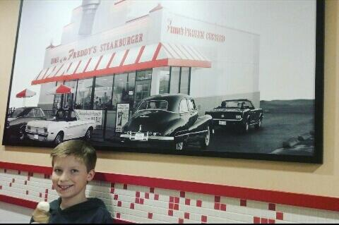 This is Gatlin Jessop eating ice cream and standing in front of a picture on February 28, 2017