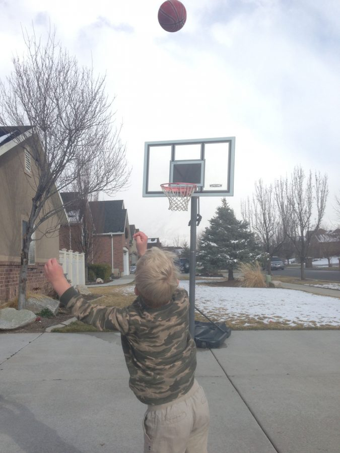Jace Iverson shooting a ball in the hoop.