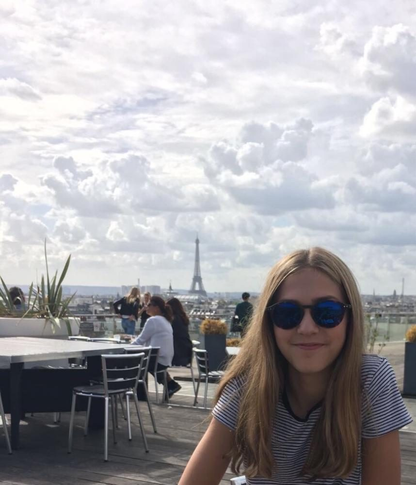 Brynn Franckowiak on top of the Parisian department store, Printemps with the Eiffel Tower in the background, on September 2016.