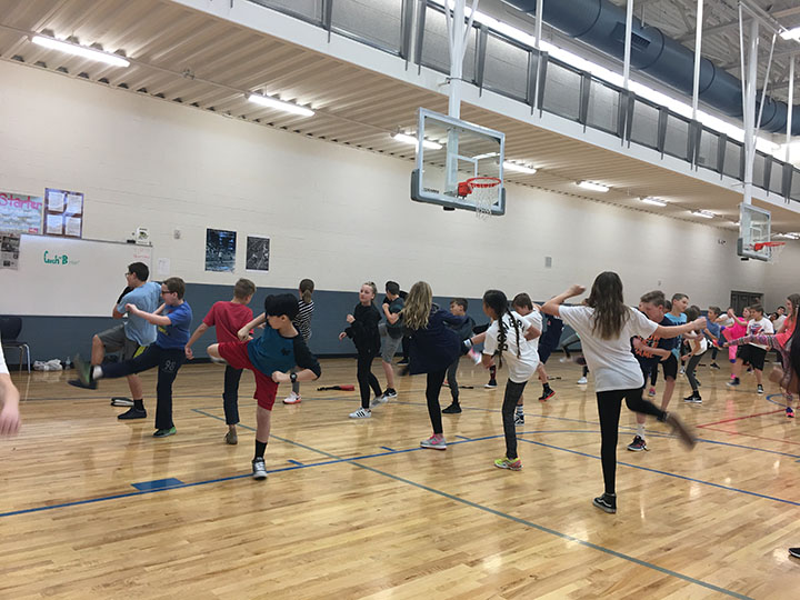 Gym students practicing their karate kick.
