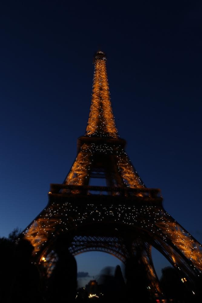 In Paris, France, the Eiffel Tower twinkling at midnight.